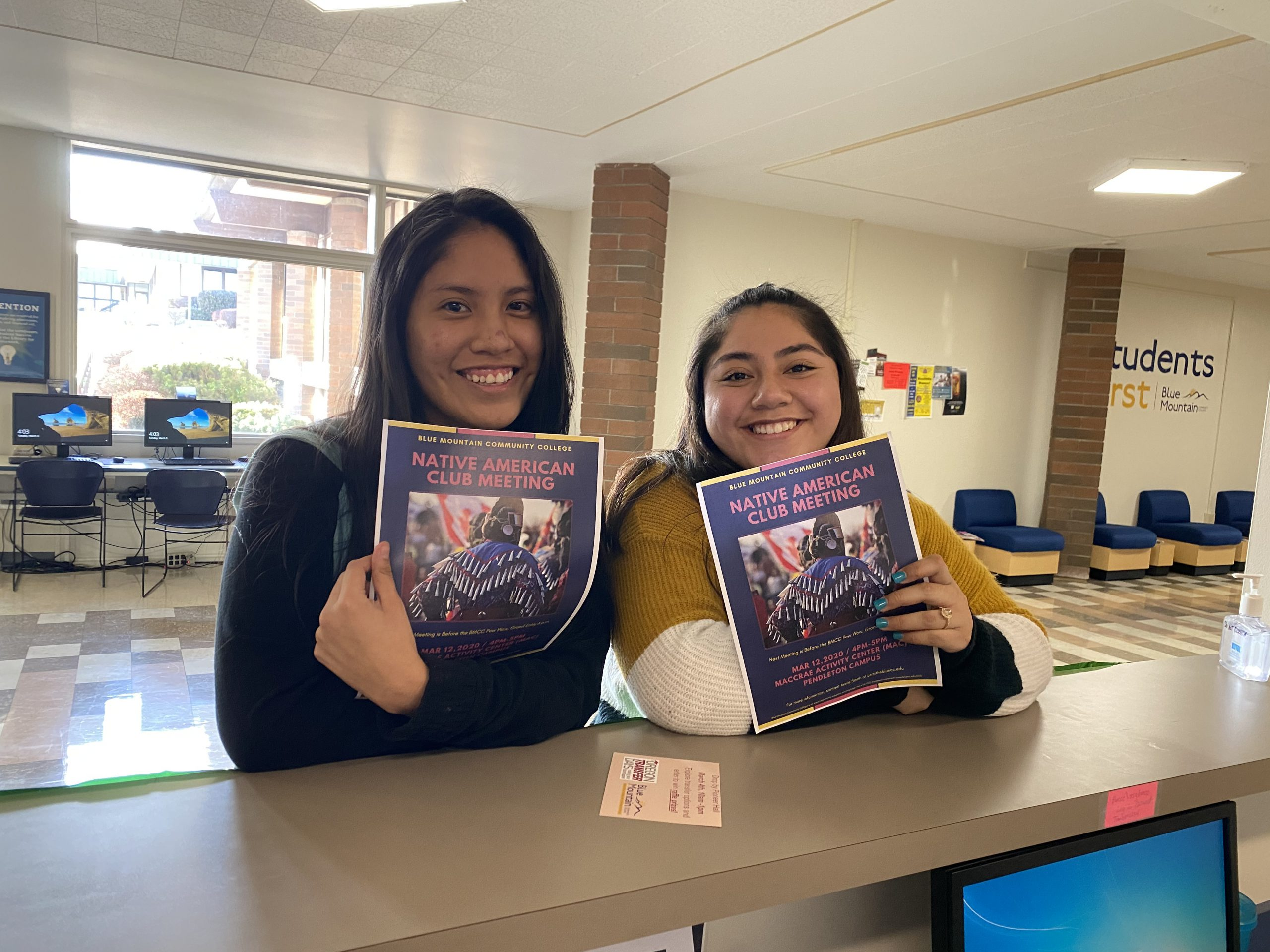 Two members of the Native American Club hold up club flyers.