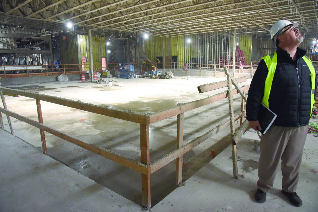 Inside a building under construction. A man, Dave Tovey, is on the far right of the frame wearing a hard hat and neon vest.