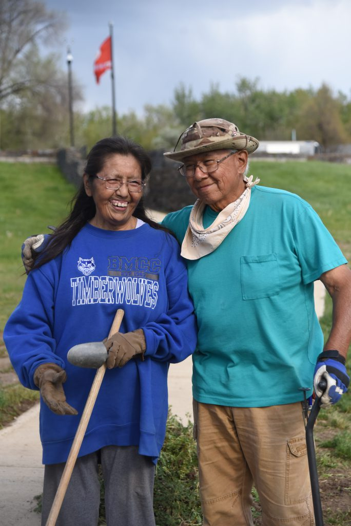 Retired couple with gardneing gear on stand before the Warriors Memorial.
