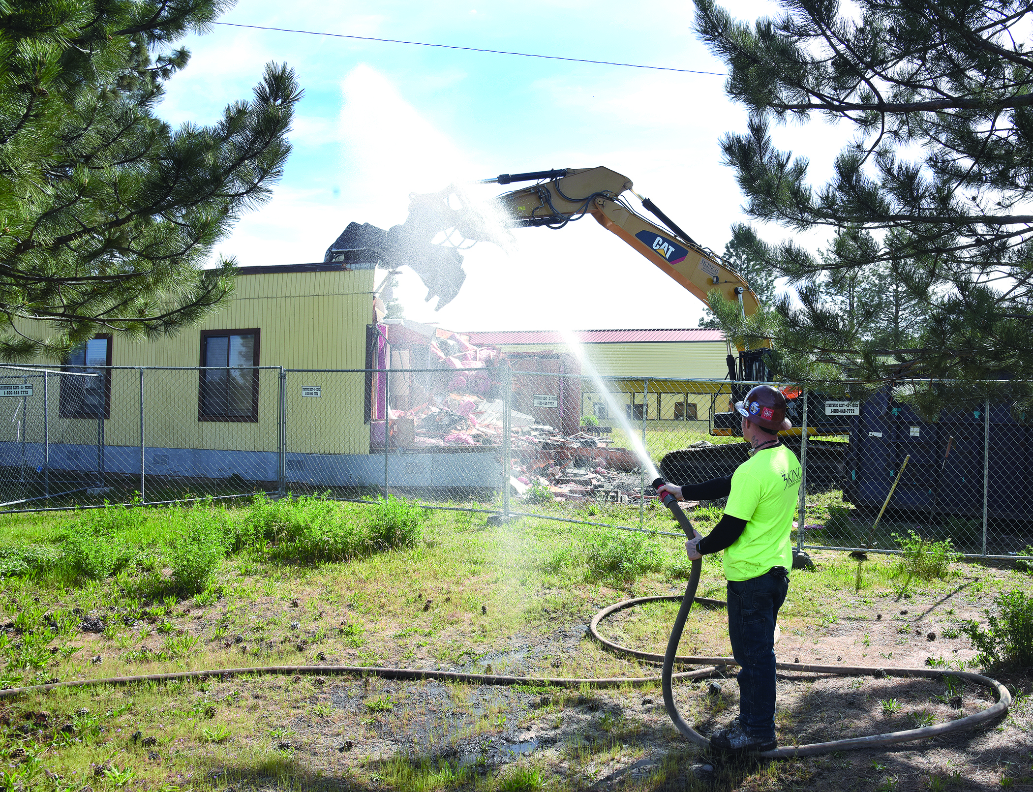 Wes Leers of Portland, who works for 3 Kings Environmental from Battle Ground, Washington, sprays water on the former accounting office for Yellowhawk Tribal Health Center. That building and several more, including the old clinic and Cay-Uma-Wa Education facility, are being razed over the next eight weeks. That will leave the July Grounds mostly empty except for the Community Center, the Longhouse and a couple of other smaller buildings.