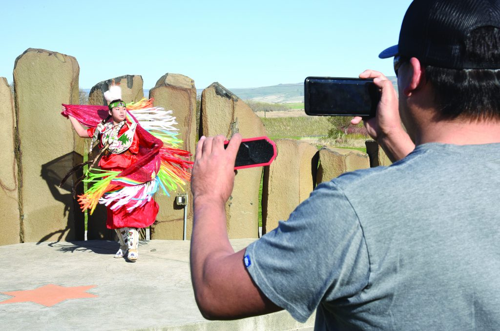 Alayna Bevis dances while her father, Jesse Bevis Sr., records a video that they submitted to a social network pow-wow site. Native Americans from across Indian Country have been participating in the activity, some of which is competitive. Alanna was dancing here in front of the Nixyaawii Governance Center.