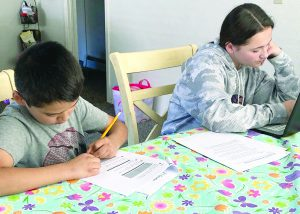 Two kids sit at the dinner table and work on homework.
