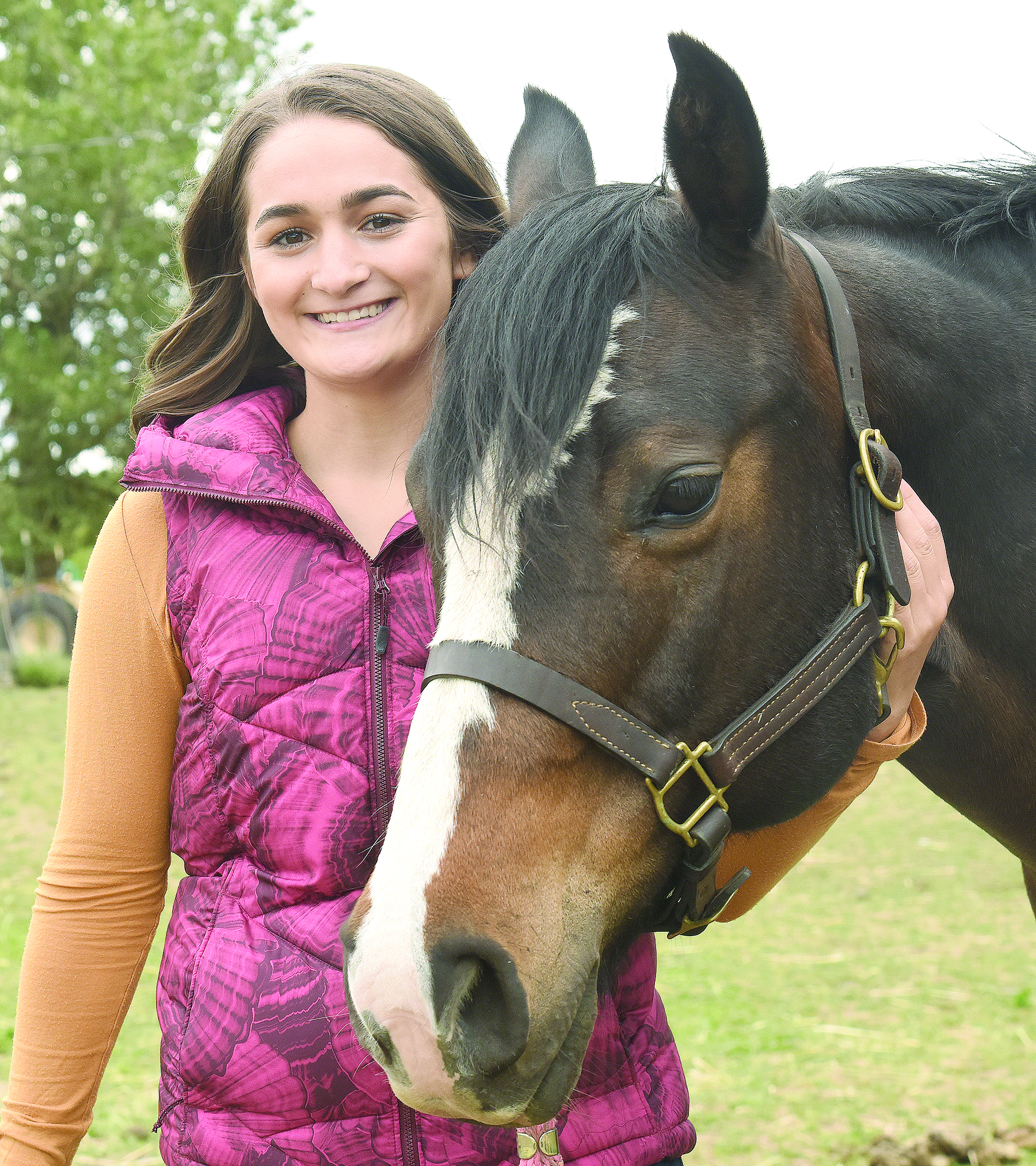 Teenager stands with her horse.