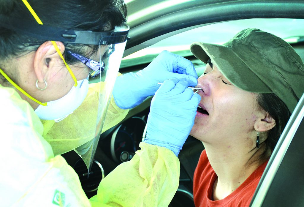 Patient getting her nose swabbed by a nurse.