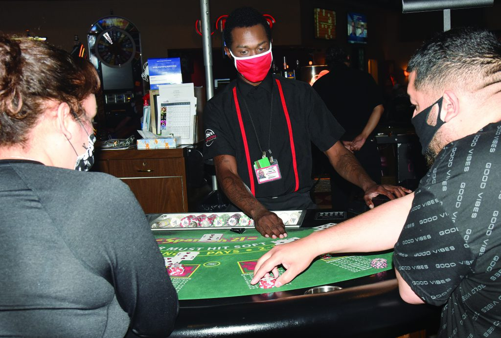 Dealer at blackjack table with two guests.