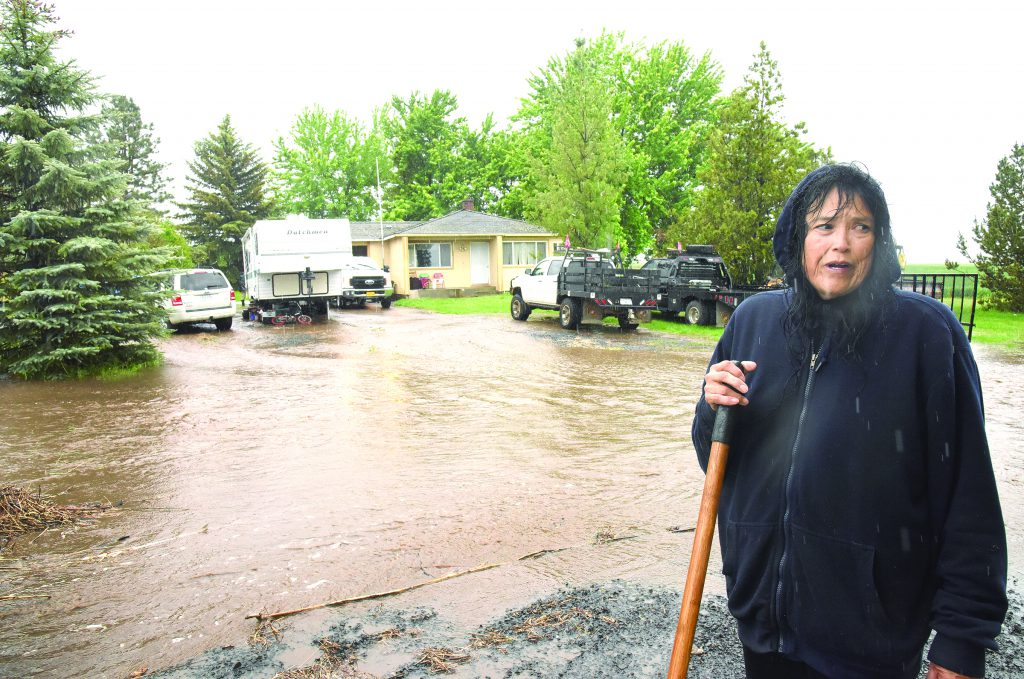 Woman standing in rain in front of her flooded front yard.